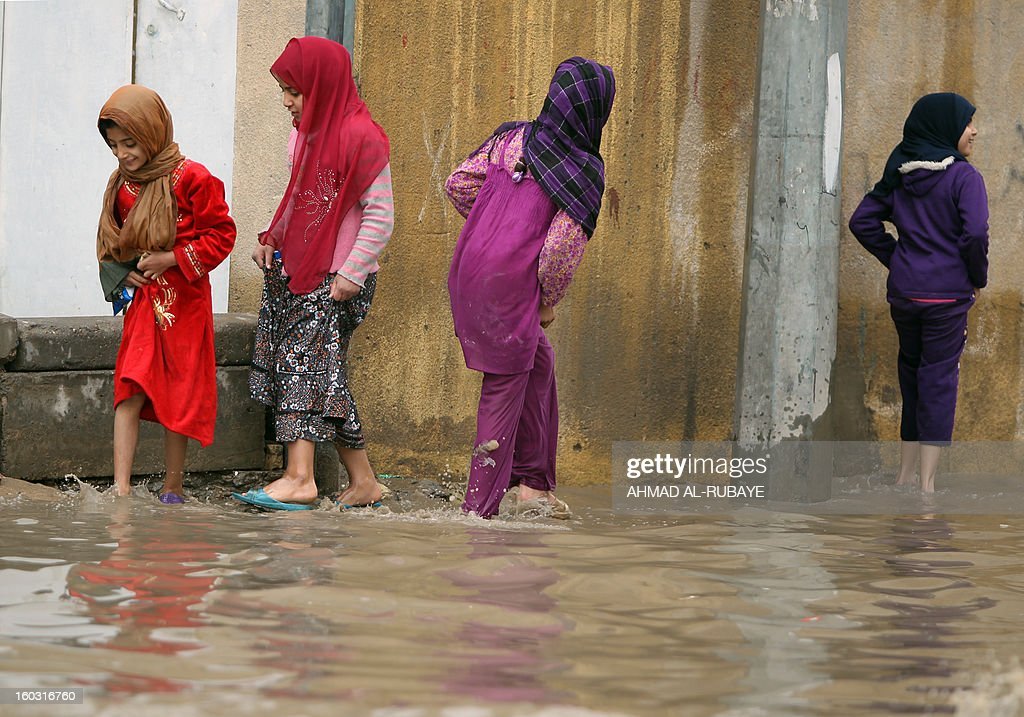Iraqi girls walk in a flooded street in Baghdad after heavy rainfall overnight on January 29, 2013. Baghdad suffered from the worst rains to hit the capital in 30 years in December 2012 which left four people dead and many of the Iraqi capital's residents struggling to cope with heavy flooding. AFP PHOTO/AHMAD AL-RUBAYE