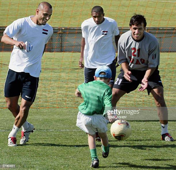 Iraqi goalkeeper Wisam Khadhum with the aid of captain Muhaned Ali try to prevent fiveyearold Daniel Stynes from scoring a goal as the Iraqi team...