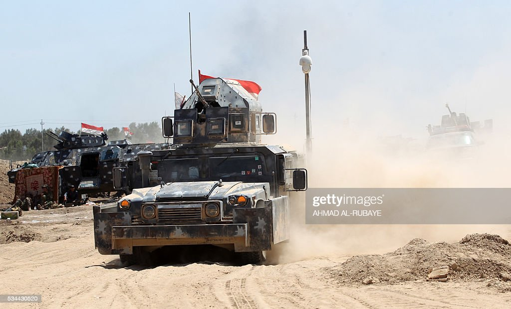 Iraqi government forces advance near al-Sejar village, north-east of Fallujah, on May 26, 2016, as they take part in a major assault to retake the city from the Islamic State (IS) group. Tens of thousands of security forces are deployed in the Fallujah area for an assault aimed at retaking the city from the Islamic State group. Fallujah, which lies only 50 kilometres (30 miles) west of Baghdad, has been out of government control since January 2014 and is one of only two remaining major Iraqi cities still in IS hands, the other being Mosul. / AFP / AHMAD