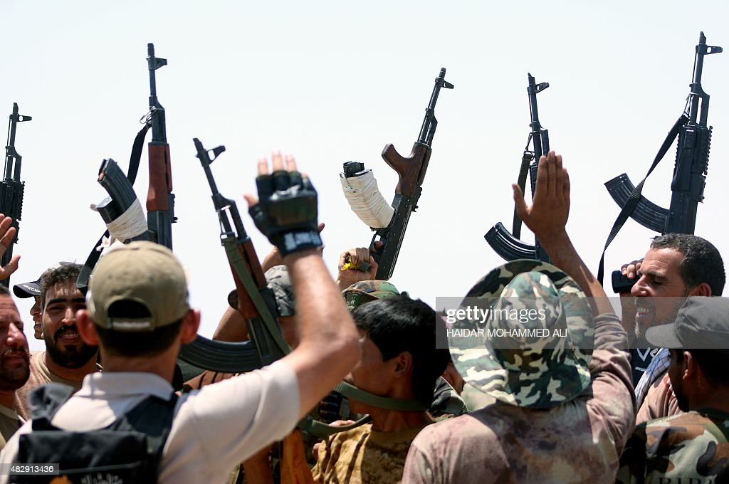 Iraqi government forces and members of the Popular Mobilisation units paramilitary forces that are dominated by Iranbacked Shiite militias raise...