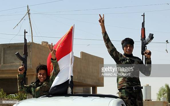 TOPSHOT Iraqi government forces celebrate in the town of Sharqat around 80 kilometres south of the city of Mosul on September 23 the day after they...