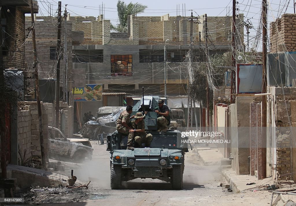 Iraqi government forces drive their military vehicle in Fallujah after forces retook the embattled city from the Islamic State group on June 26, 2016. Iraqi Prime Minister Haider al-Abadi urged all Iraqis to celebrate the recapture of Fallujah by the security forces and vowed the national flag would be raised in Mosul soon. While the battle has been won, Iraq still faces a major humanitarian crisis in its aftermath, with tens of thousands of people who fled the fighting desperately in need of assistance in the searing summer heat. ALI