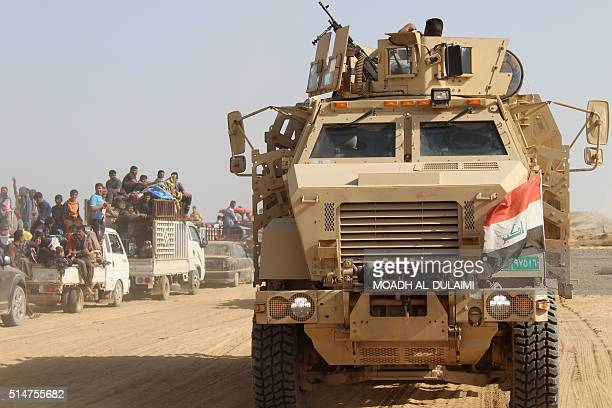 Iraqi government forces evacuate civilians on March 10 2016 after retaking the town of Zankura northwest of Ramadi from the Islamic State jihadist...
