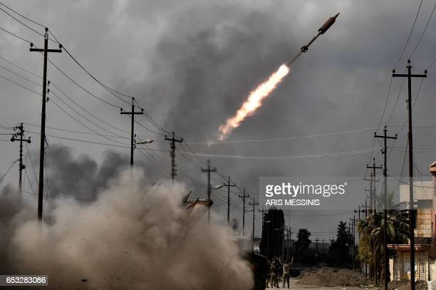 TOPSHOT Iraqi government forces fire a rocket towards Islamic State group positions in west Mosul on March 14 as they continue to advance in the...