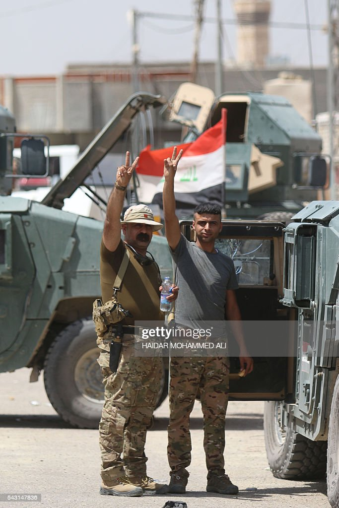 Iraqi government forces flash the 'V' for victory sign in Fallujah after they retook the embattled city from the Islamic State group on June 26, 2016. Iraqi Prime Minister Haider al-Abadi urged all Iraqis to celebrate the recapture of Fallujah by the security forces and vowed the national flag would be raised in Mosul soon. While the battle has been won, Iraq still faces a major humanitarian crisis in its aftermath, with tens of thousands of people who fled the fighting desperately in need of assistance in the searing summer heat. ALI