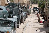 Iraqi government forces gather next to their vehicles on June 27 2016 in western Fallujah 50 kilometres from the Iraqi capital Baghdad after Iraqi...