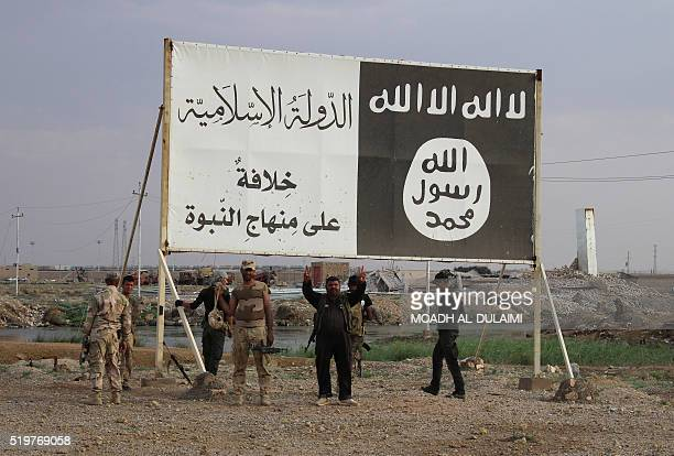 Iraqi government forces gather under a billboard bearing slogans of the Islamic State group and its trademark flag in the town of Heet in Iraq's...