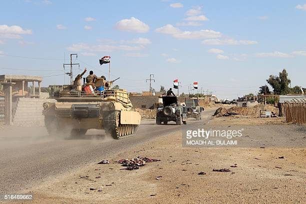 Iraqi government forces gesture from their vehicles in the village of Mohammadi a few miles north of Heet in Iraq's western province of Anbar on...