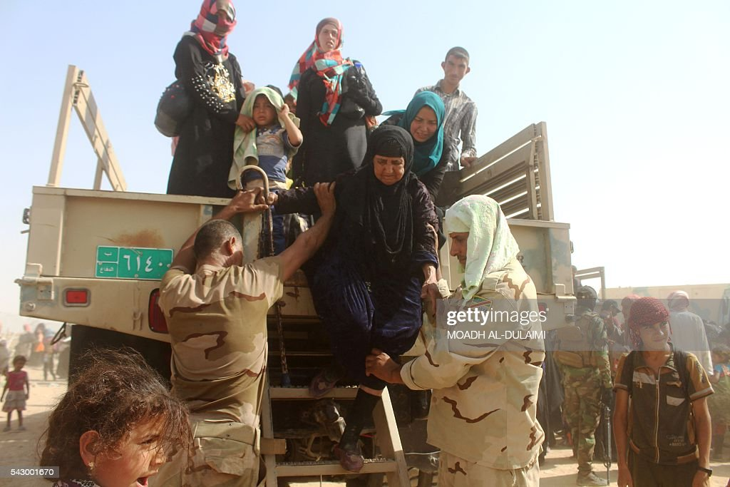 Iraqi government forces help displaced people from al-Buthiab area north of Ramadi as they arrive at a makeshift camp, 18 kms west of the capital of Anbar province, where they are taking shelter, on June 25, 2016. Iraqi government forces retook control of the city of Ramadi from the Islamic State (IS) group in February 2016 but sporadic IS attacks there have continued. / AFP / MOADH