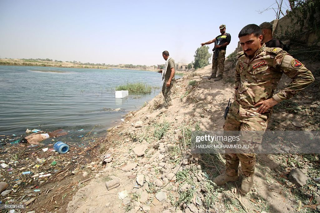 Iraqi government special forces look at bodies floating along the shore of the Euphrates river as he patrols an area in the center of Fallujah, 50 kilometres (30 miles) from the Iraqi capital Baghdad, after Iraqi forces retook the embattled city from the Islamic State group on June 27, 2016. Iraqi forces took the Islamic State group's last positions in the city of Fallujah on June 26, 2016, establishing full control over one of the jihadists' most emblematic bastions after a month-long operation. ALI