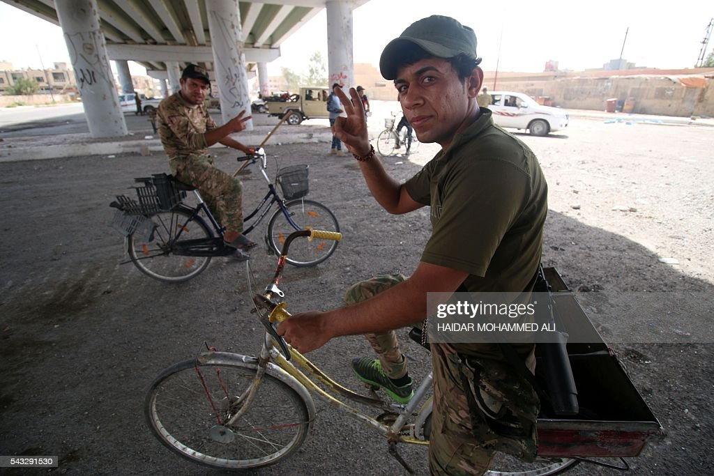 Iraqi government forces on their bicycles flash the sign of victory as they secure an area in western Fallujah, 50 kilometres (30 miles) from the Iraqi capital Baghdad, after Iraqi forces retook the embattled city from the Islamic State group on June 27, 2016. Iraqi forces took the Islamic State group's last positions in the city of Fallujah on June 26, 2016, establishing full control over one of the jihadists' most emblematic bastions after a month-long operation. ALI