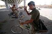 Iraqi government forces on their bicycles flash the sign of victory as they secure an area in western Fallujah 50 kilometres from the Iraqi capital...