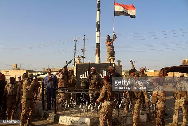 Iraqi government forces raise the Iraqi flag as they celebrate in the alBakr neighbourhood north of Hit in Iraq's Anbar province after they cleared...