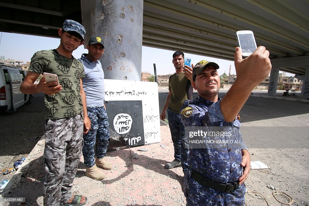 Iraqi government forces take pictures with their phones as they secure an area in western Fallujah, 50 kilometres (30 miles) from the Iraqi capital Baghdad, after Iraqi forces retook the embattled city from the Islamic State group on June 27, 2016. west of the city Iraqi forces took the Islamic State group's last positions in the city of Fallujah on June 26, 2016, establishing full control over one of the jihadists' most emblematic bastions after a month-long operation. ALI
