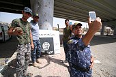 Iraqi government forces take pictures with their phones as they secure an area in western Fallujah 50 kilometres from the Iraqi capital Baghdad after...