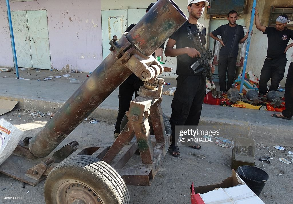 Iraqi gunmen stand on September 10 2014 next to a rebelmade mortar launcher left behind by Islamic State fighters in Barwanah in the Anbar province...