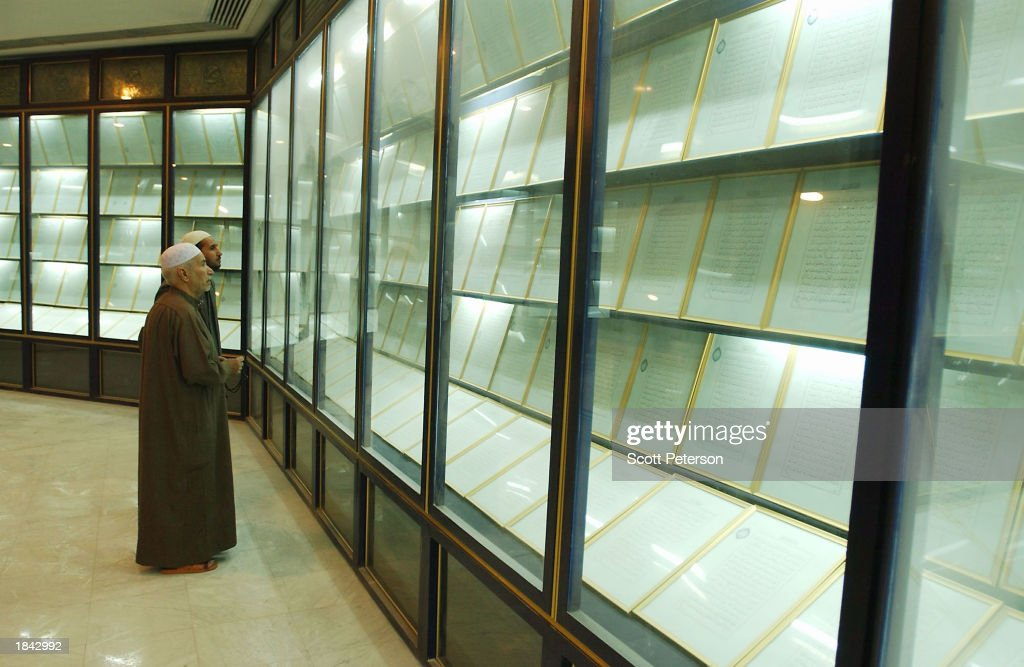 Iraqi Imams, or mosque prayer leaders, view the 605-page Koran written with 24 liters of Iraqi leader Saddam Hussein's own blood donated over three years at the 'Mother of All Battles' Umm al-Maarik mosque March 11, 2003 in Baghdad, Iraq. The mosque was built with minarets styled after Scud missiles. The complex includes a lake in the shape of a map of the Arab world.