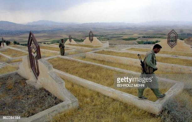 Iraqi Kurd peshmerga or militia fighters walk 20 October 2002 at the mass grave spot for civilian victims of the 1988 poison gas attack on the town...