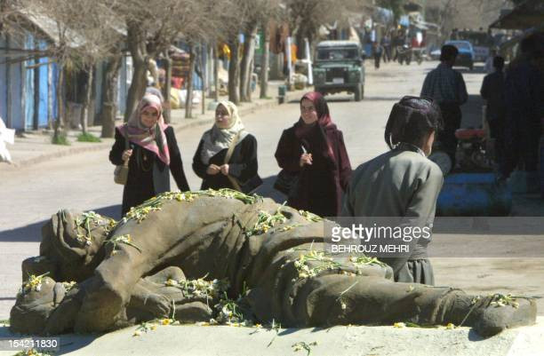 Iraqi Kurd women pass by a memorial monument of a dead Kurdish man protecting his child during the poison gas attack by Iraqi President Saddam...