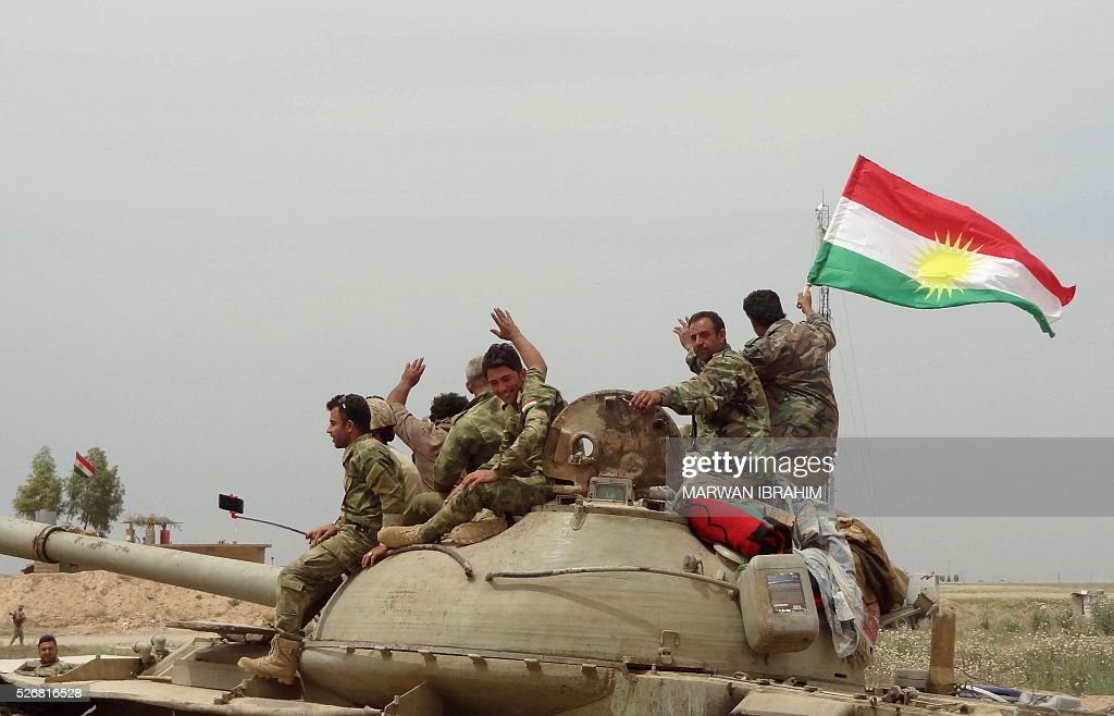 Iraqi Kurdish and Turkmen Shiite forces from the Popular Mobilisation units sit on top of a tank on May 1, 2016 in the northern Iraqi town of al-Bashir after they recaptured the town from the control of the Islamic State (IS) group. Pressure for an operation to retake the town had grown in March after IS launched a chemical attack from Bashir on the nearby town of Taza that killed at least three children. / AFP / Marwan IBRAHIM