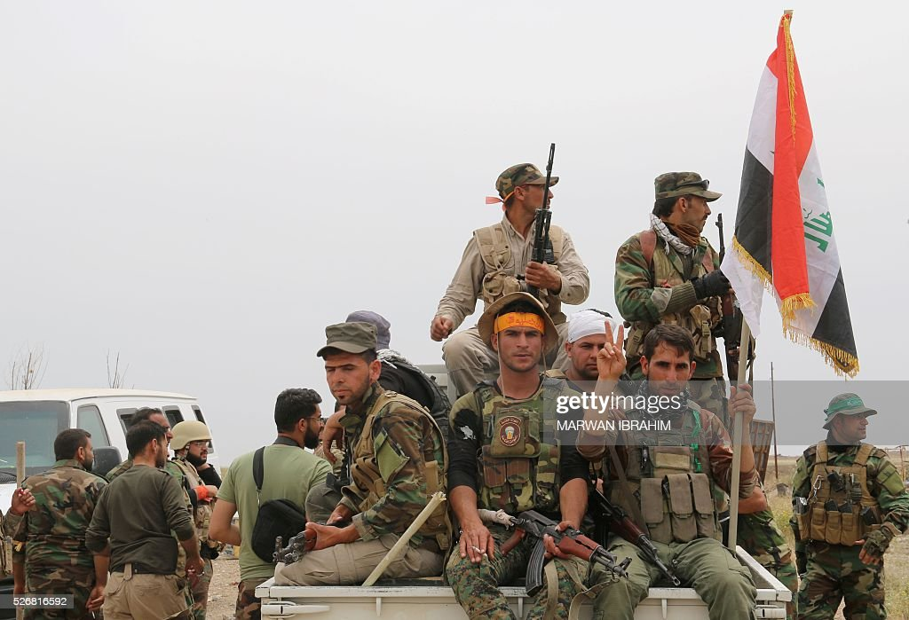 Iraqi Kurdish and Turkmen Shiite forces from the Popular Mobilisation units flash the sign for victory on May 1, 2016 in the northern Iraqi town of al-Bashir after they recaptured the town from the control of the Islamic State (IS) group. Pressure for an operation to retake the town had grown in March after IS launched a chemical attack from Bashir on the nearby town of Taza that killed at least three children. / AFP / Marwan IBRAHIM