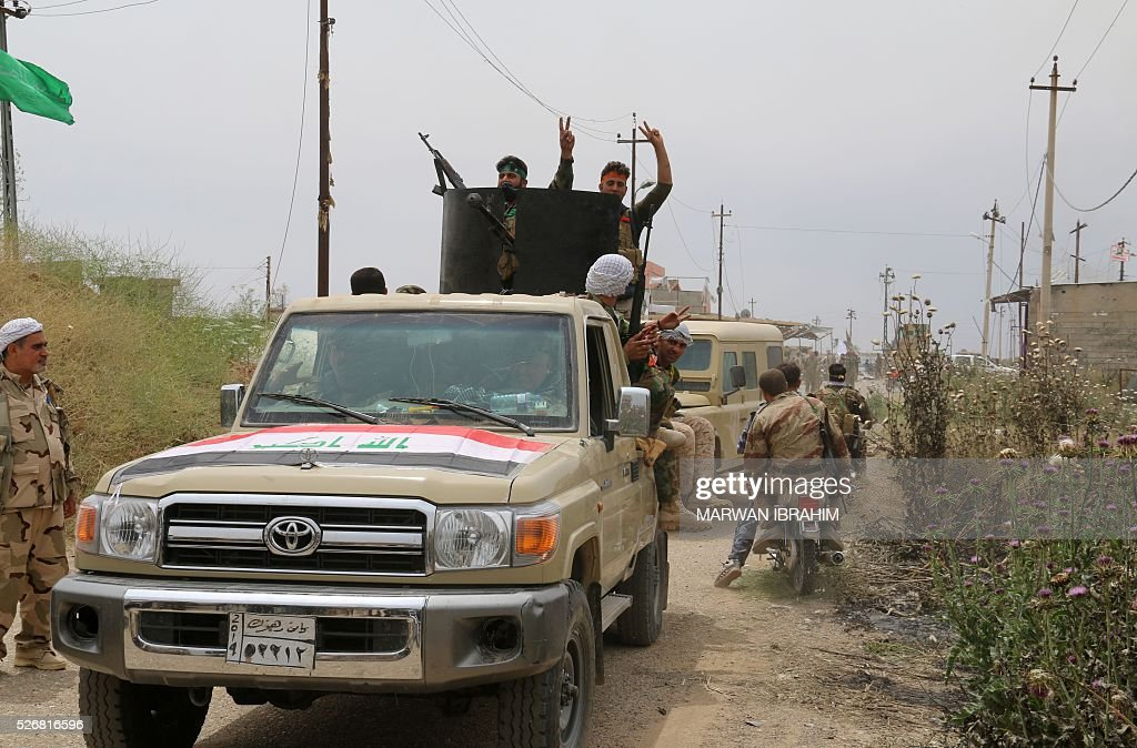 Iraqi Kurdish and Turkmen Shiite forces from the Popular Mobilisation units flash the sign for victory as they drive in convoy on May 1, 2016 in the northern Iraqi town of al-Bashir after they recaptured the town from the control of the Islamic State (IS) group. Pressure for an operation to retake the town had grown in March after IS launched a chemical attack from Bashir on the nearby town of Taza that killed at least three children. / AFP / Marwan IBRAHIM