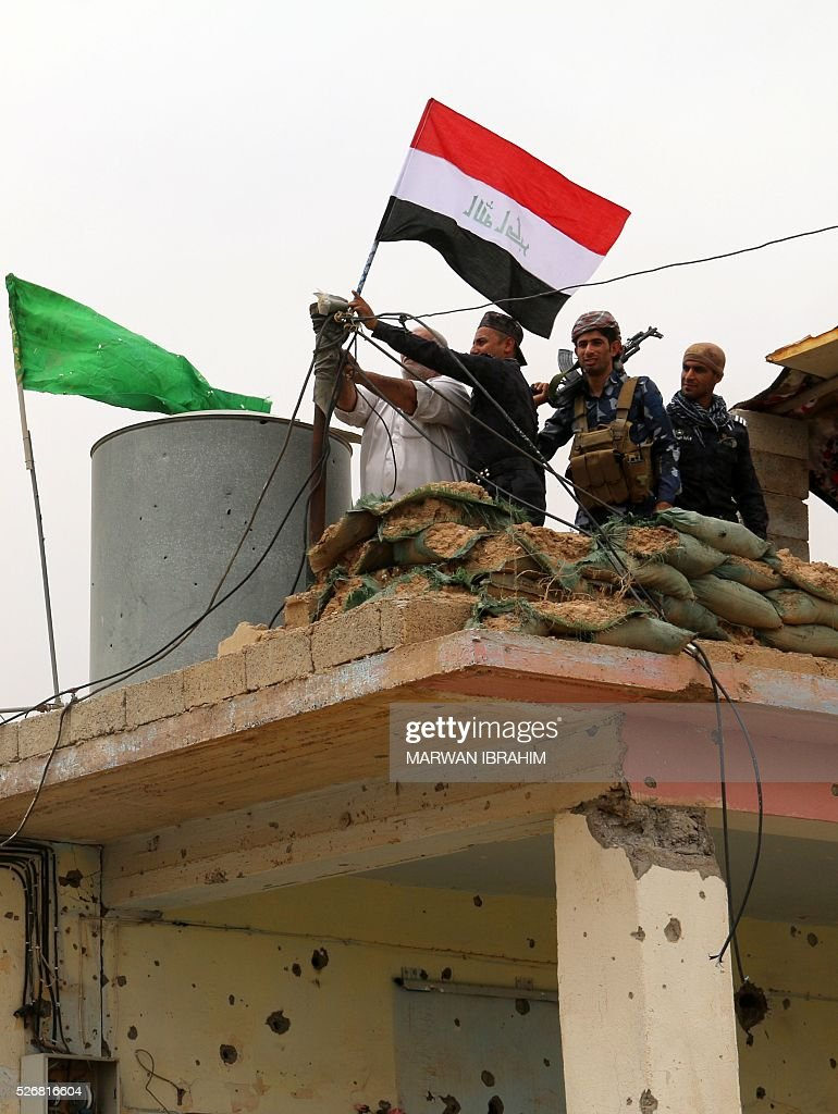 Iraqi Kurdish and Turkmen Shiite forces from the Popular Mobilisation units put the Iraqi flag on top of a building on May 1, 2016 in the northern Iraqi town of al-Bashir after they recaptured the town from the control of the Islamic State (IS) group. Pressure for an operation to retake the town had grown in March after IS launched a chemical attack from Bashir on the nearby town of Taza that killed at least three children. / AFP / Marwan IBRAHIM