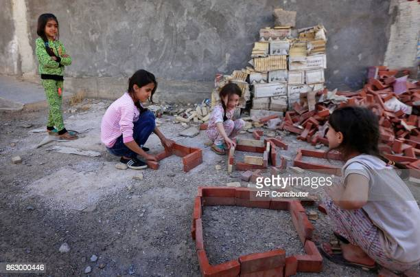 Iraqi Kurdish children play at an unfinished housing project where displaced people fleeing violence in the northern Kirkuk province are taking...