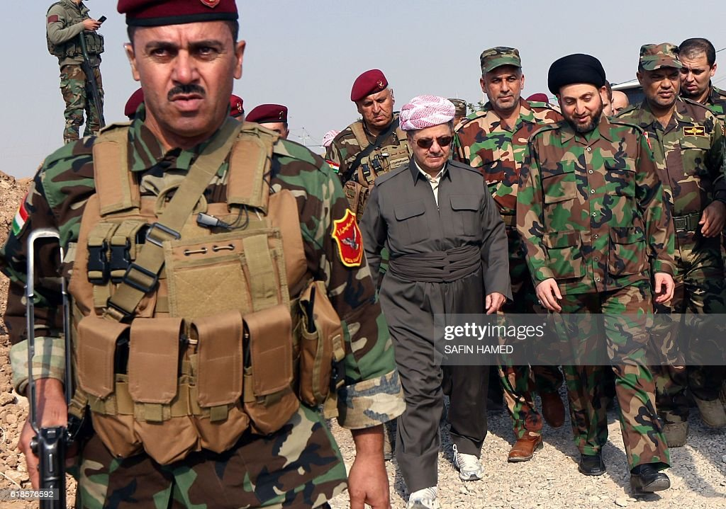 Iraqi Kurdish leader Massud Barzani (C) and Shiite Muslim leader Ammar al-Hakim (2ndR), the head of the Islamic Supreme Council of Iraq (ISCI), arrive to give a joint press conference on October 27, 2016 on the top of Mount Zardak, where Iraqi Kurdish peshmerga fighters hold a position during an operation against Islamic State (IS) group jihadists to retake the main hub of Mosul, located some 25 kilometres from Mount Zardak. Iraqi security forces and Kurdish peshmerga fighters are pushing toward Mosul along several axes and have made relatively quick progress as they approach Mosul, Iraq's second city. / AFP / SAFIN