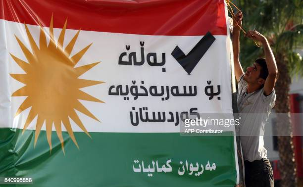 Iraqi Kurdish man hangs up a banner urging for a vote for independence in the upcoming September 2017 referendum in Arbil the capital of the...