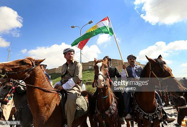 Iraqi Kurdish men one holding the Kurdish flag ride their horses past the Citadel during a commemoration marking the 23th anniversary of the uprising...