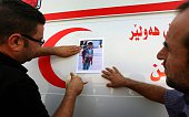 Iraqi Kurdish men stick a photo of a Kurdish migrant who died strangled in a lorry in Austria alongside other migrants on an ambulance during a...