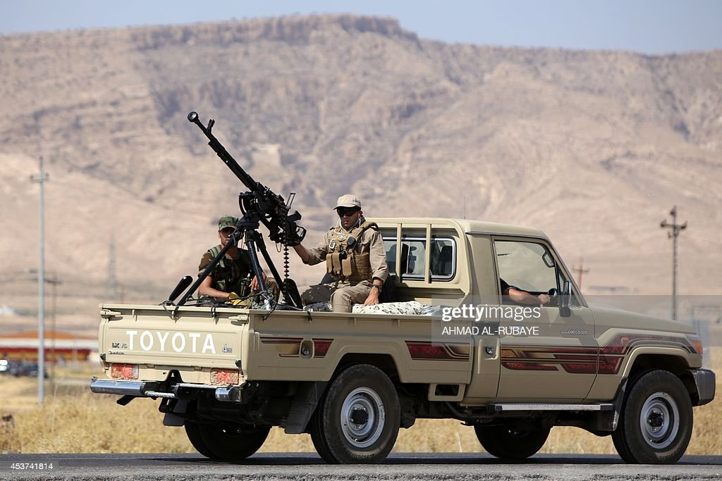 Iraqi Kurdish Peshmerga fighters drive a truck with a machine gun mounted on the back as they head to the Mosul dam on the Tigris river that they...