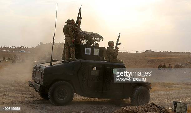 Iraqi Kurdish Peshmerga fighters drive their military vehicle after they reportedly captured several villages from Islamic State group jihadistst on...