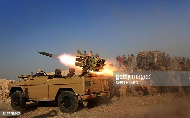 TOPSHOT Iraqi Kurdish Peshmerga fighters fire a multiple rocket launcher from a position in Sheikh Ali village near the town of Bashiqa some 25...