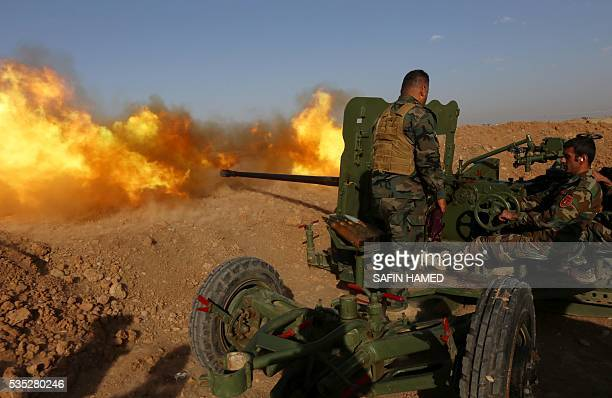 TOPSHOT Iraqi Kurdish Peshmerga fighters fire an antitank cannon on the front line near Hasan Sham village some 45 kilometres east of the city of...