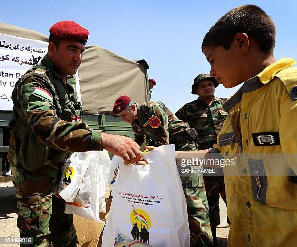 Iraqi Kurdish Peshmerga fighters give gifts to children who fled violence in the northern city of Tal Afar due to attacks by Islamic State jihadists...