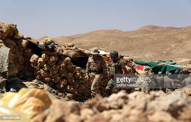 Iraqi Kurdish Peshmerga fighters guard a position behind sandbags at the frontline of fighting against Islamic State group's militants near the...
