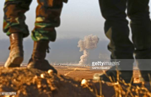 TOPSHOT Iraqi Kurdish Peshmerga fighters stand in an area near the town of Bashiqa some 25 kilometres north east of Mosul as smoke billows on October...