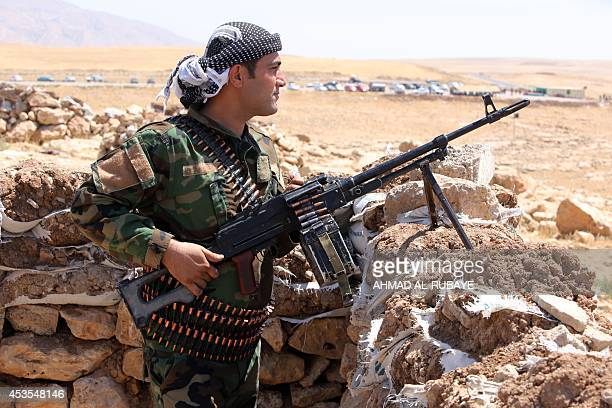 Iraqi Kurdish Peshmerga fighters take position as they monitor the area from their front line position in Bashiqa a town 13 kilometres northeast of...