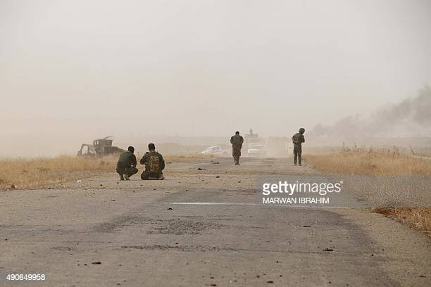Iraqi Kurdish Peshmerga fighters walk down a road after they reportedly captured several villages from Islamic State group jihadistst on the...