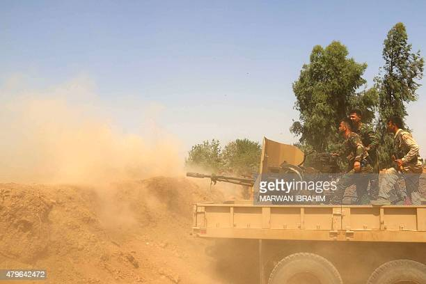 Iraqi Kurdish Peshmerga forces and Popular Mobilisation units fire towards Islamic State group fighters positions on July 6 in the village of Mura in...