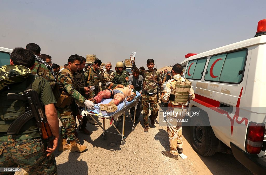 Iraqi Kurdish Peshmerga forces carry a wounded comrade during an operation near Hasan Sham village, some 45 kilometres east of the city of Mosul, aimed at retaking areas from the Islamic State group on May 29, 2016. The 'peshmerga-led ground offensive, backed by international coalition warplanes' started before dawn, the Kurdistan Region Security Council (KRSC) said. The fresh push against the jihadist organisation comes a week after Iraqi forces launched an operation against Fallujah, IS's only other major urban hub in Iraq. / AFP / SAFIN