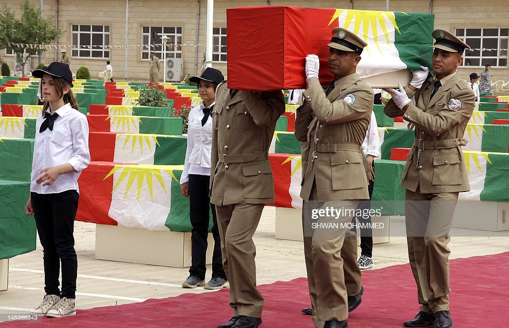 Iraqi Kurdish police officers carry one of 730 coffins draped with the Kurdish flag and containing the remains of victims of the Anfal massacre, during a ceremony in Sulaimaniyah in northern Iraq, on May 28, 2012. The coffins contain the remains of victims of the brutal 1988 'Anfal' (Spoils of War) campaign carried out by Saddam Hussein's forces, in which an estimated 182,000 people have died.