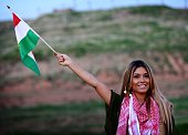 Iraqi Kurdish pop singer Dashni Murad known as the Shakira of Kurdistan poses with a Kurdistan flag during a visit to Kurdish Peshmerga fighters...