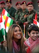 Iraqi Kurdish pop singer Dashni Murad known as the Shakira of Kurdistan poses with a young boy during a visit to Kurdish Peshmerga fighters...