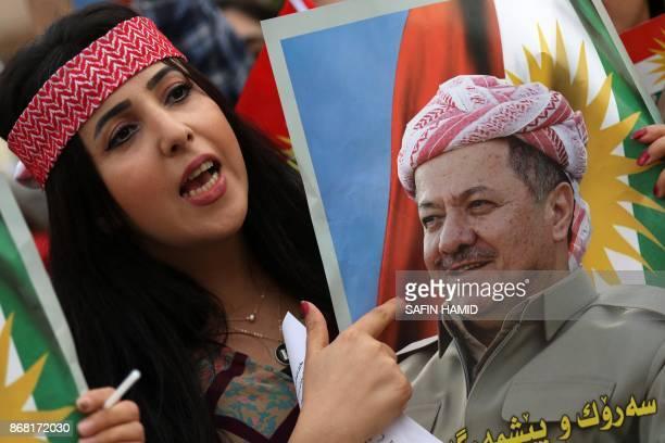 Iraqi Kurdish students of the Salahaddin University hold posters of Iraqi Kurdish leader Massud Barzani during a protest in his support in Arbil the...