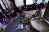 Iraqi Kurdish women cook food for families who fled the violence in the the northern province of Nineveh at a mosque in Arbil the capital of the...
