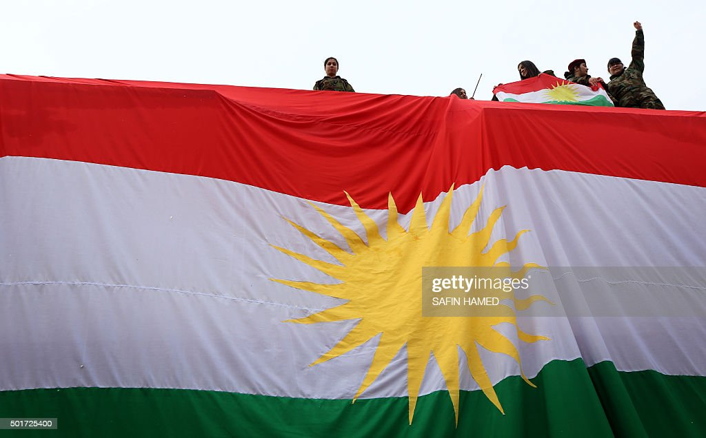TOPSHOT Iraqi Kurdish youths wave a national flag as they stand above a giant flag of Kurdistan during celebrations of Flag Day on December 17 2015...