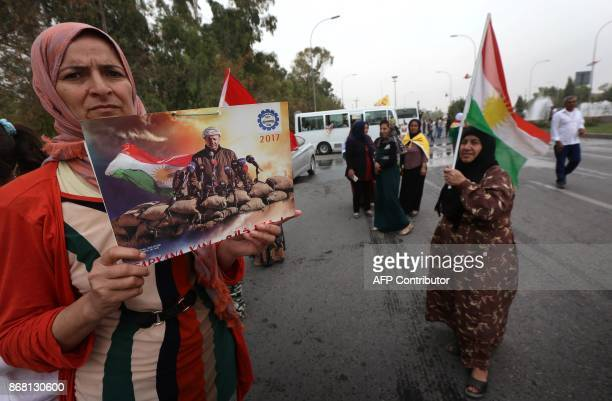 Iraqi Kurds hold frames portraying the Iraqi Kurdish leader Massud Barzani during a protest in support of him in Arbil the capital of autonomous...